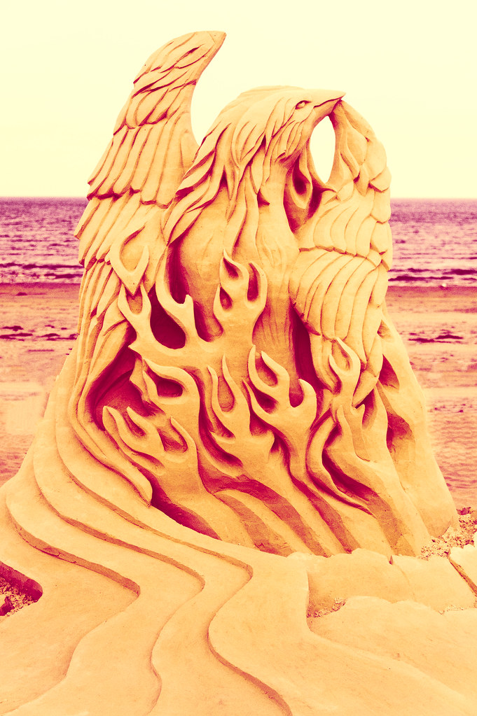 Phoenix Rising by Eric Kilby -- a photo of a sand sculpture portraying a phoenix arising out of the flames